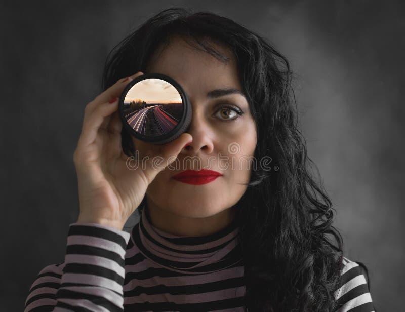 Женщина брюнета с объективом фотоаппарата в ее глазе, с фотографией стоковые изображения