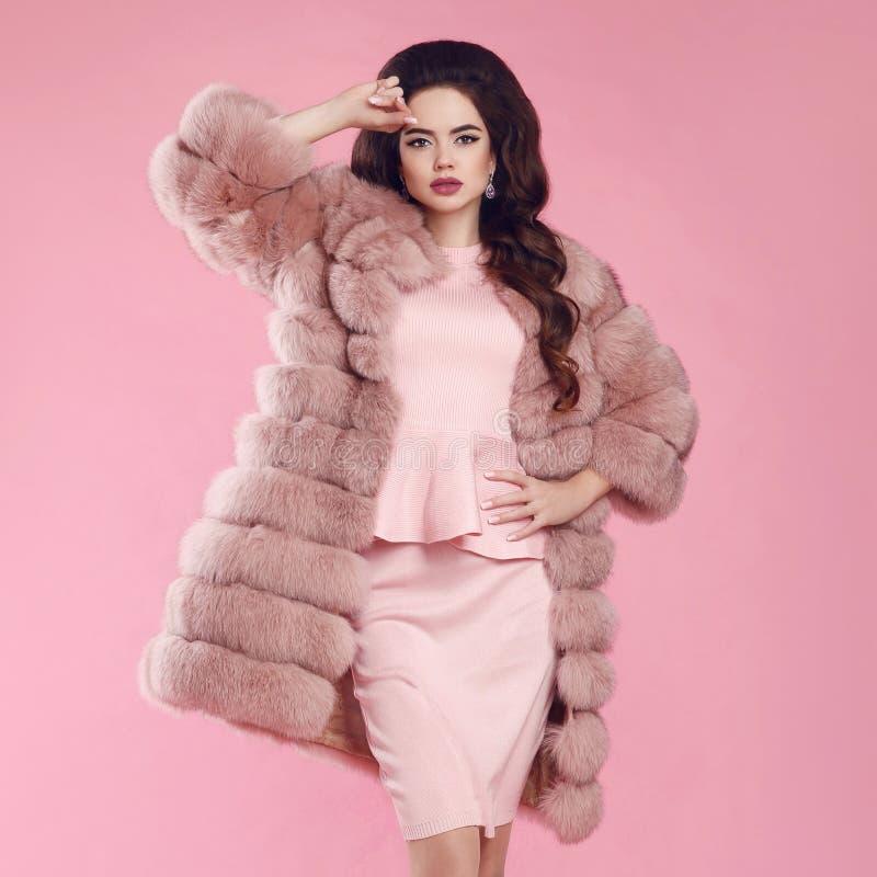 Женщина брюнет в меховой шыбе над пинком фото студии моды идет стоковые изображения rf