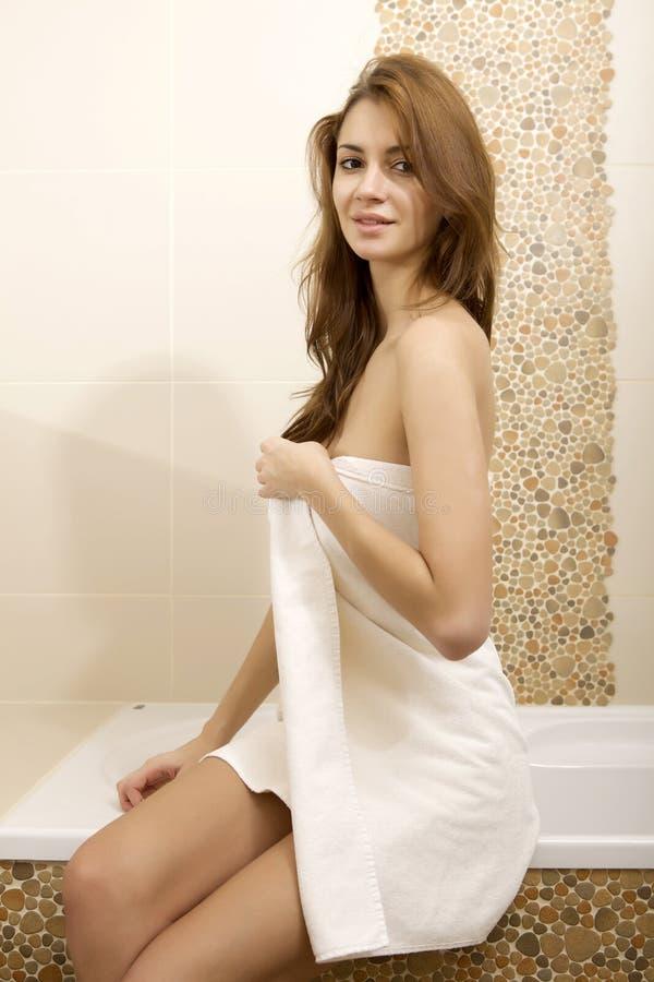 Женщина брюнет в домашней ванной комнате стоковое фото rf