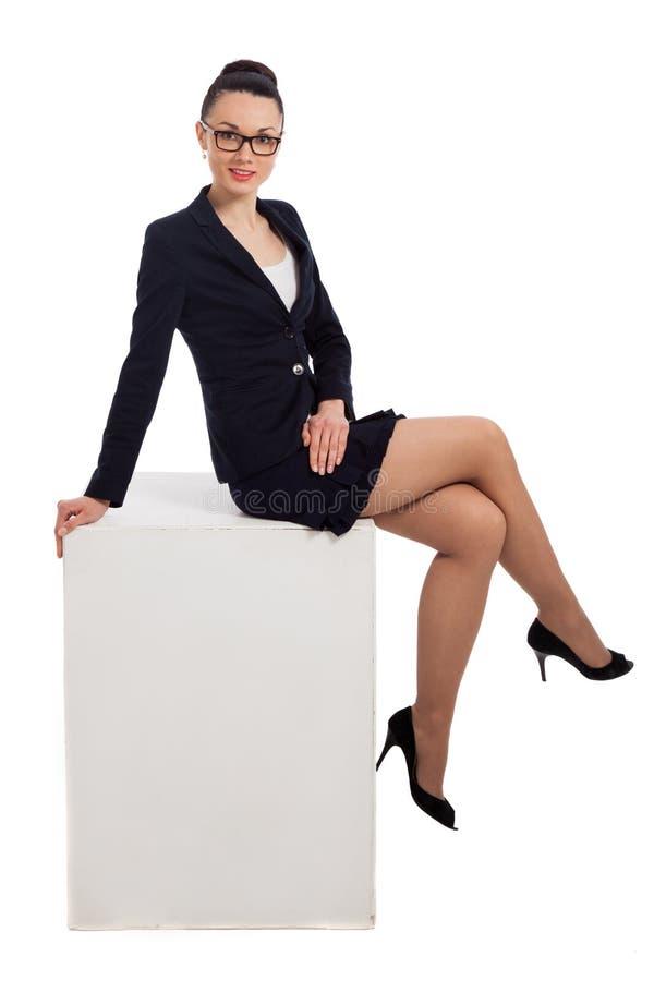 Женщина брюнет в черной юбке и куртке сидя на кубе стоковые изображения