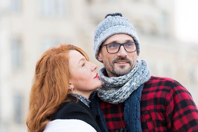 Женщина брюнет идя целующ человека Красная женщина волос смотря к стороне парней портрет пар счастливый Бородатый парень в стекла стоковая фотография rf