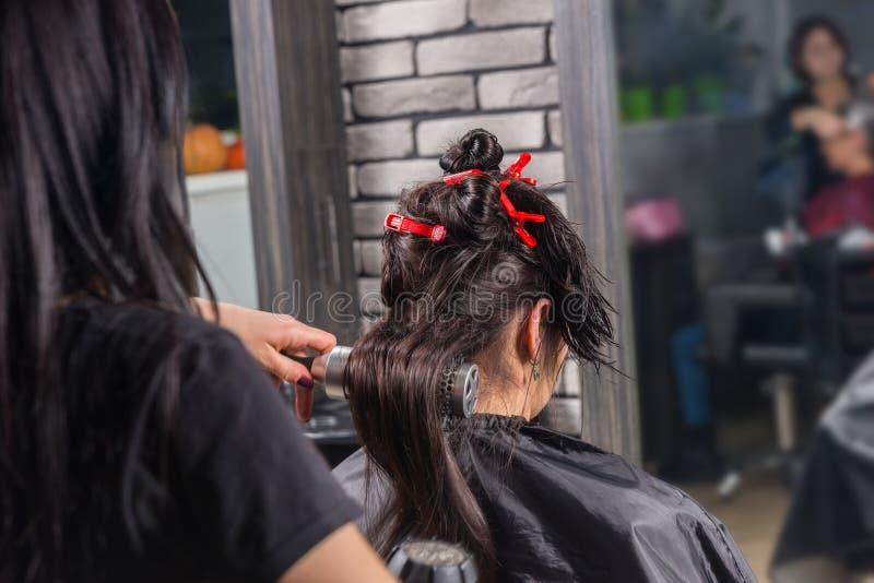Женщина брюнет имея влажные волосы быть почищенным щеткой и высушенным usin стилизатора стоковое изображение