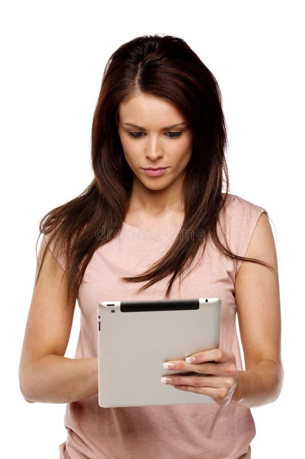 Женщина брюнет используя таблетку компьютера стоковое изображение rf