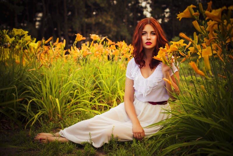 Женщина брюнет кавказская в белом платье на парке в красных и желтых цветках на заходе солнца лета держа цветки сидя на gr стоковое изображение