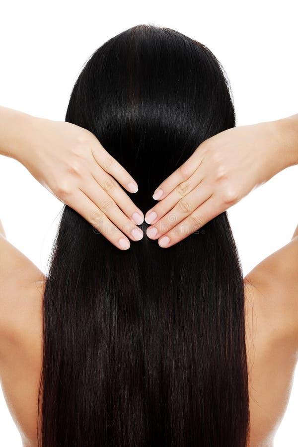 женщина брюнет касаясь ее волосам стоковое фото