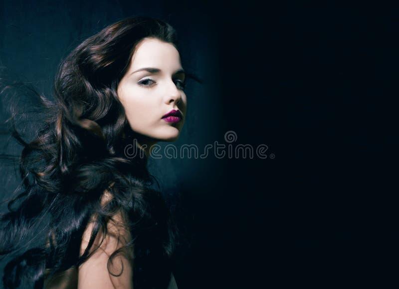 Женщина брюнет красоты молодая с курчавыми волосами летания, femme смертоносным стоковое фото rf