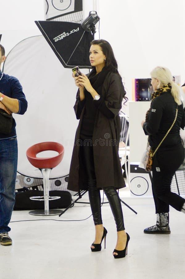 Женщина брюнет парфюмерии Intercharm XXI международная и выставки косметик молодая с модным стилем причёсок новым стоковое фото
