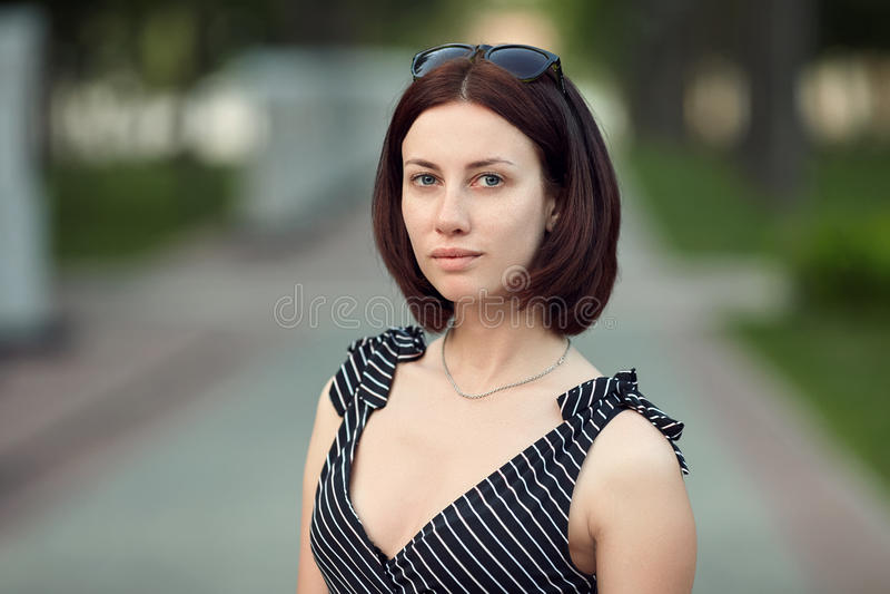 Женщина брюнет портрета образа жизни взрослая прелестная свежая смотря без составляет hairdo bob представляя парк вечера показыва стоковое фото