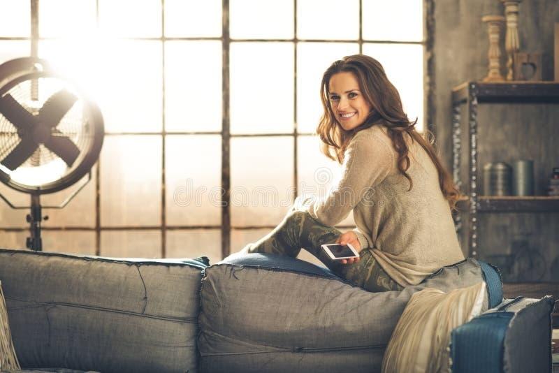 Женщина брюнет при телефон сидя на софе стоковая фотография