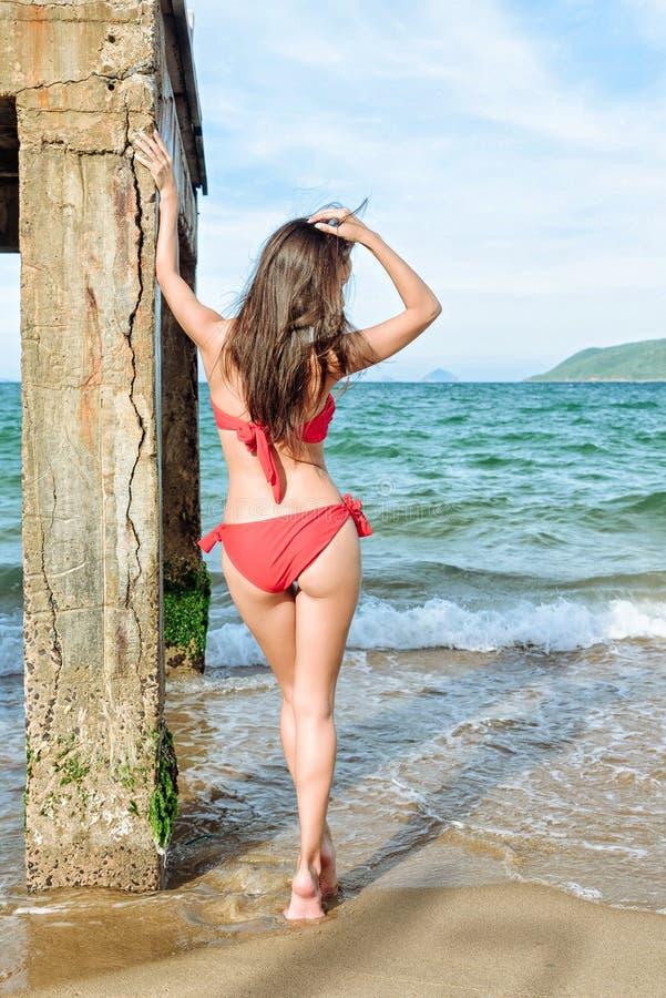 Женщина брюнет стоя близко столбец пристани стоковое изображение