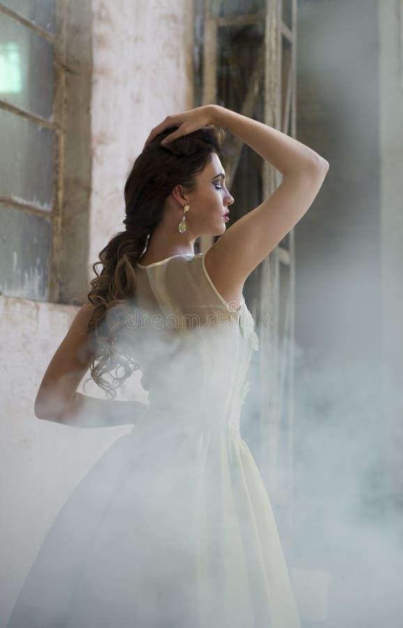 Женщина брюнет стоя между туманом рядом с деревенскими промышленными зданиями стоковая фотография rf
