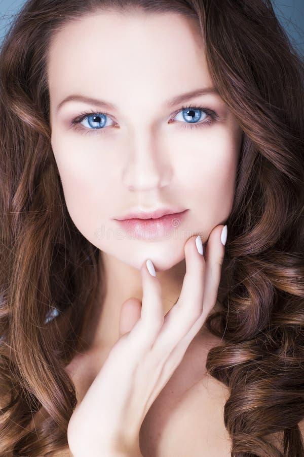 Женщина брюнет с голубыми глазами снаружи составляет, естественные безупречные кожа и руки около ее стороны стоковое изображение