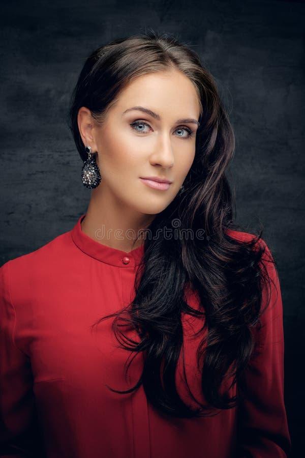 Женщина брюнет с развевая волосами в красной рубашке стоковое фото rf