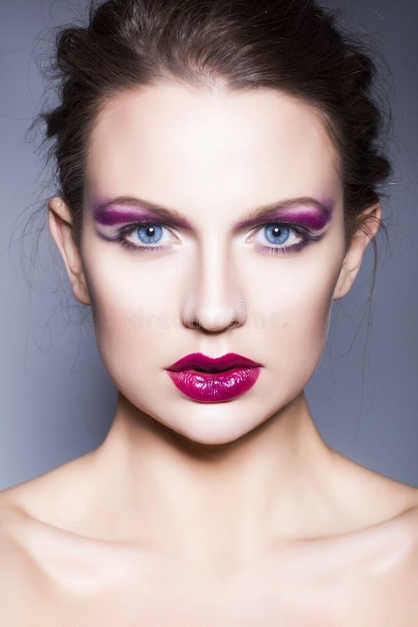 Женщина брюнет с творческим составляет фиолетовые губы, голубые глазы и вьющиеся волосы теней глаза польностью красные с ее рукой стоковая фотография rf