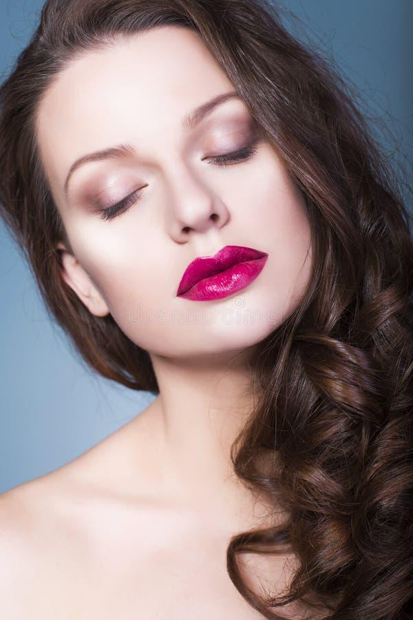 Женщина брюнет с творческим составляет фиолетовые губы, голубые глазы и вьющиеся волосы теней глаза польностью красные с ее рукой стоковое фото