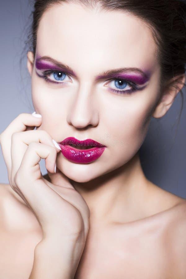 Женщина брюнет с творческим составляет фиолетовые губы, голубые глазы и вьющиеся волосы теней глаза польностью красные с ее рукой стоковые фотографии rf