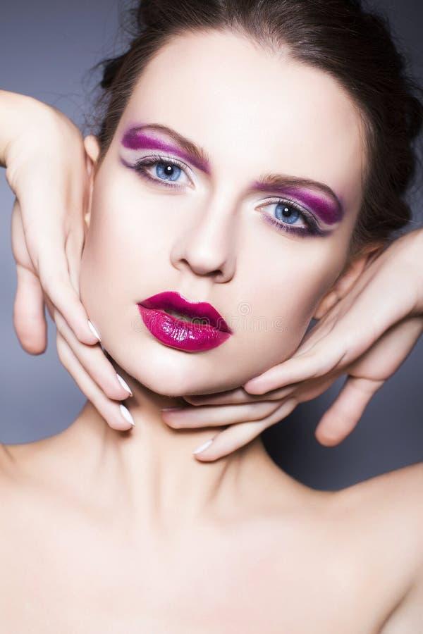 Женщина брюнет с творческим составляет фиолетовые губы, голубые глазы и вьющиеся волосы теней глаза польностью красные с ее рукой стоковое фото rf