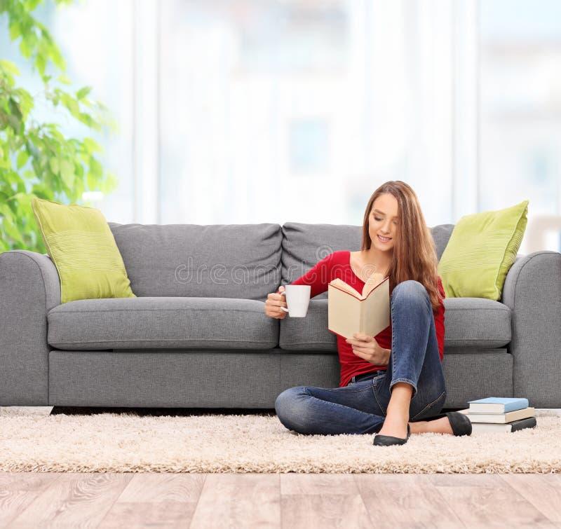 Женщина брюнет читая книгу и выпивая кофе стоковое изображение