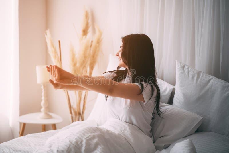 Женщина будя протягивать в кровати в раннем утре стоковые изображения rf