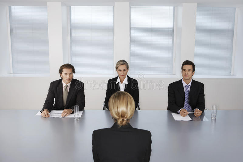 Женщина будучи интервьюированным бизнесменами стоковые фотографии rf