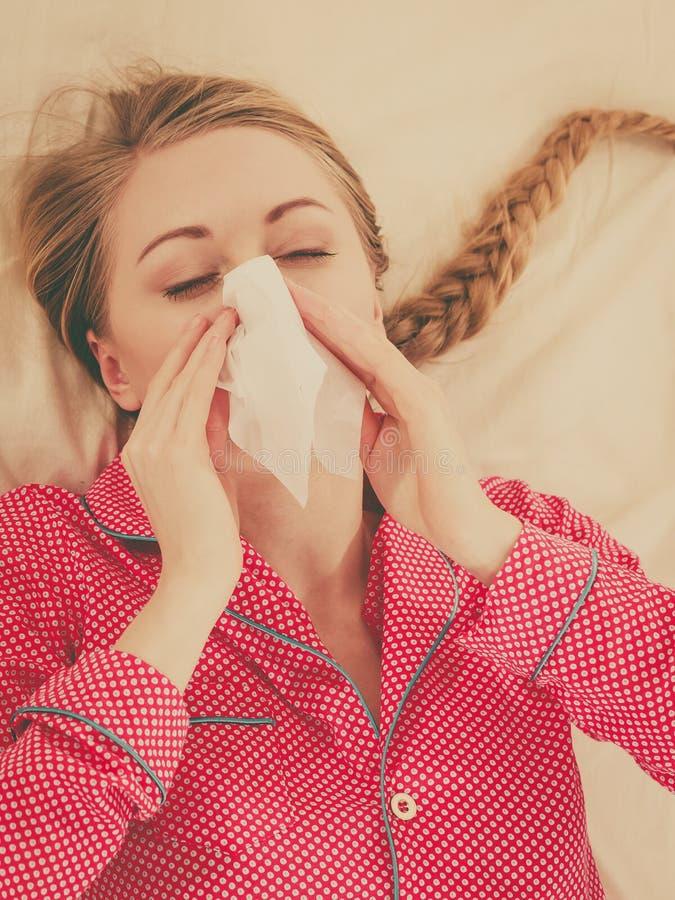 Женщина быть больной имеющ грипп лежа на кровати стоковые фотографии rf