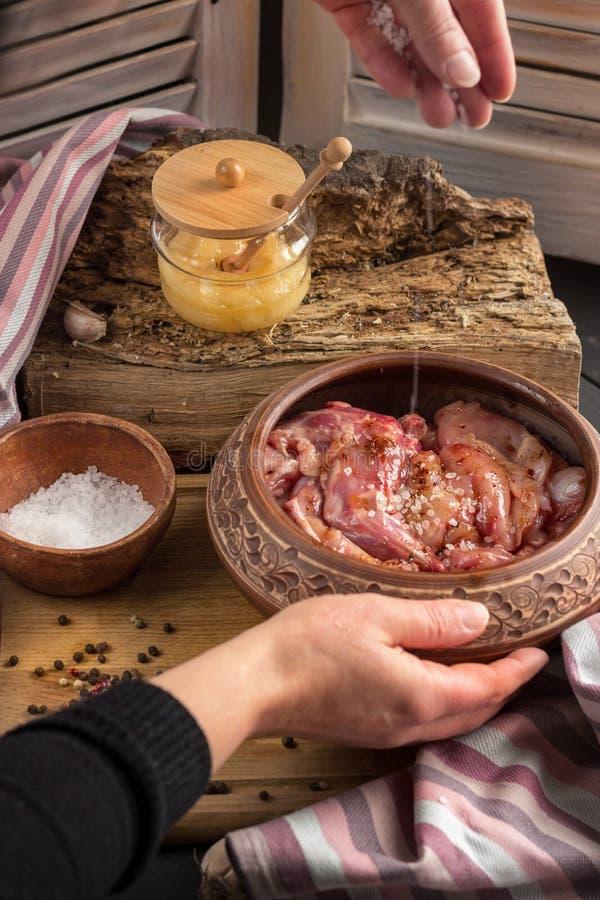 Женщина варит кролика жаркого Процесс варить мясо Куски мяса посолены и смазаны с соусом меда стоковое изображение