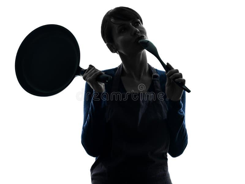 Женщина варя держащ силуэт сковороды думая стоковые изображения