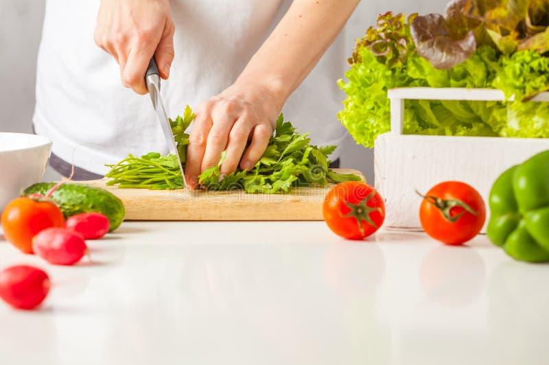 Женщина варя здоровую еду, салат отрезка зеленый vegetable Здоровый l стоковое фото