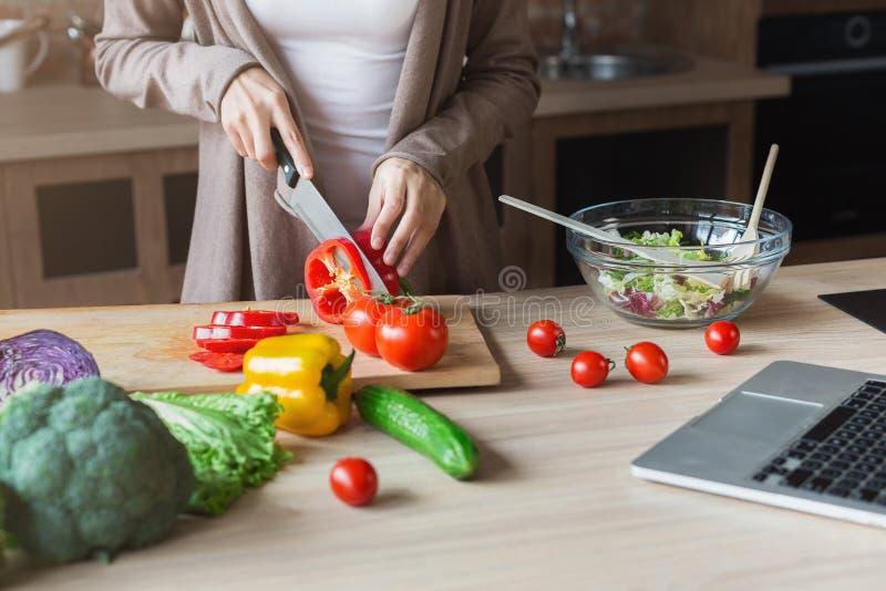 Женщина варя здоровый салат и используя компьтер-книжку дома стоковые фото
