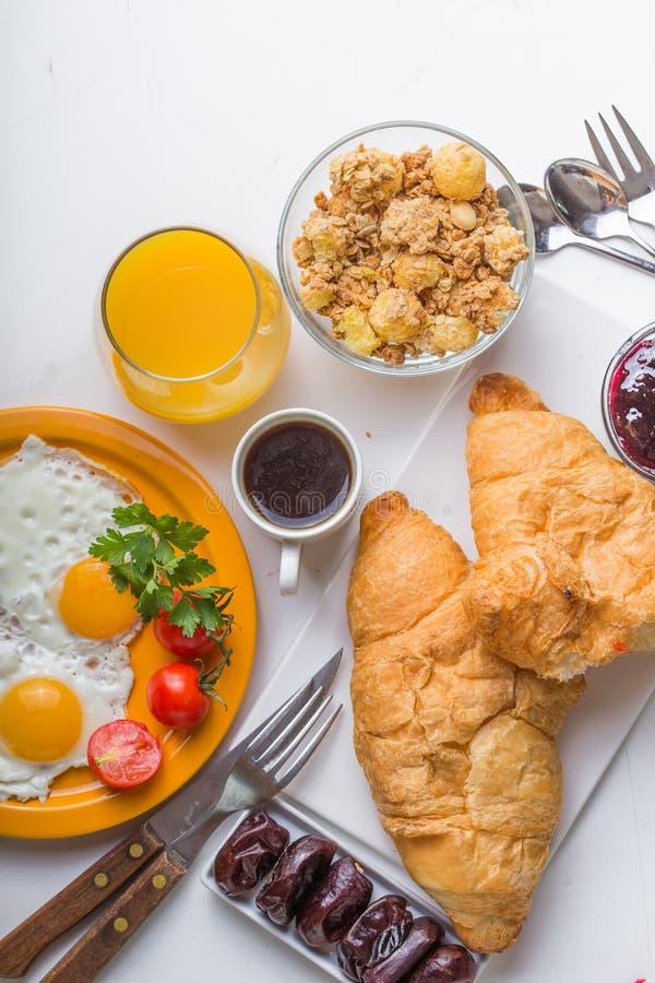Женщина варя ингридиенты завтрака завтрака здоровые, рамку еды Granola, яичко, даты, гайки, плодоовощи, варенье, ягоды, кофе, сок стоковая фотография