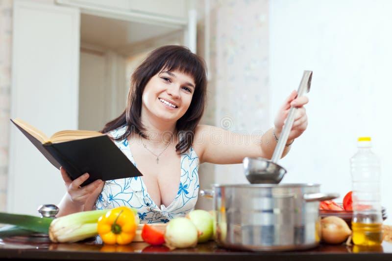 Женщина варя с книгой стоковое фото