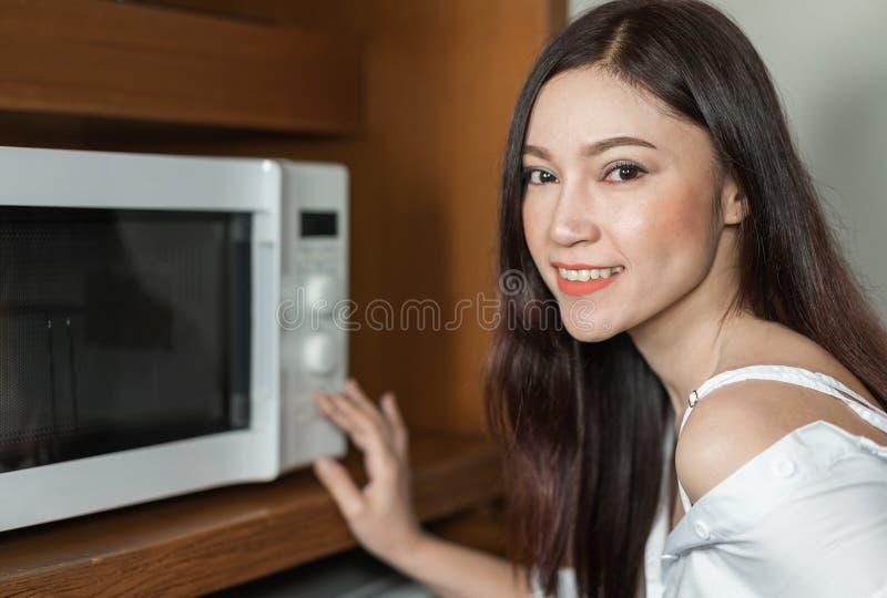 Женщина варя с микроволной в комнате кухни стоковое фото