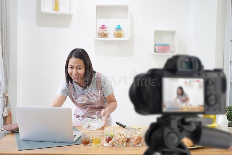 Женщина варя с получением на ноутбуке в кухне, с записью делая видео стоковое фото