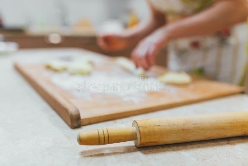 Женщина варя торты в предпосылке кухни стоковые изображения