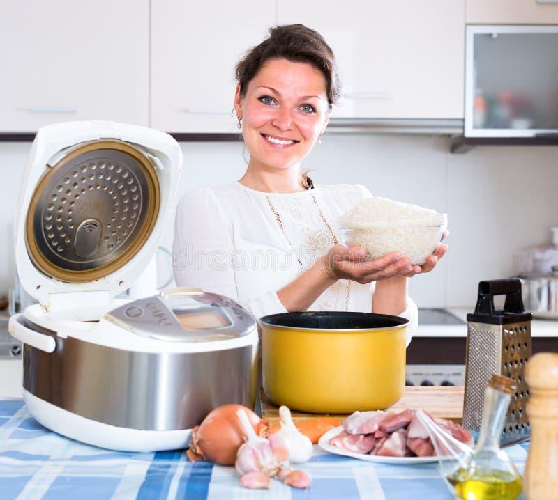 Женщина варя pilaf в multicooker стоковые изображения
