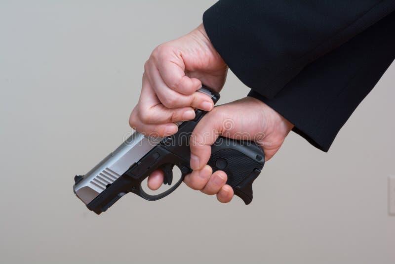 Женщина взводя курок оружию руки стоковые фото
