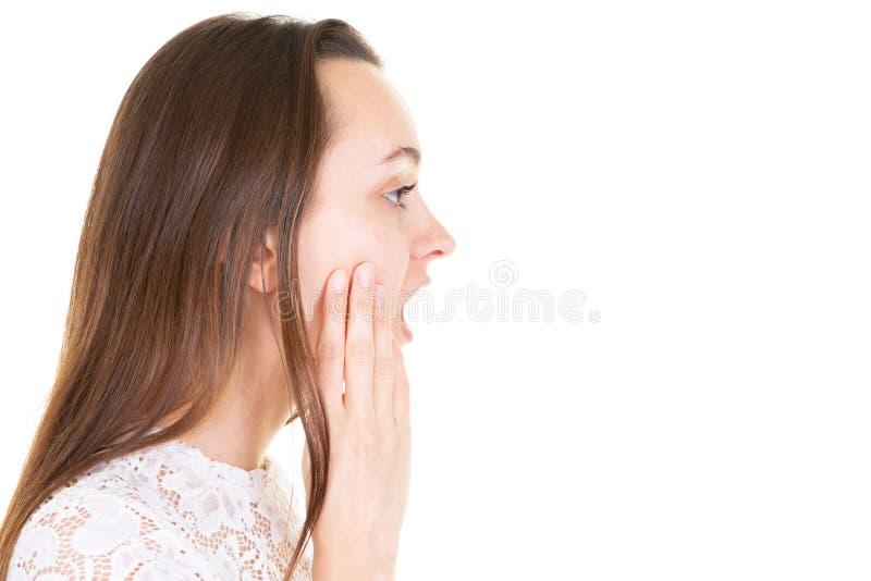Женщина вида сбокуого профиля молодая удивленная с длинными волосами кладя ее руки на ее сторону стоковые изображения rf