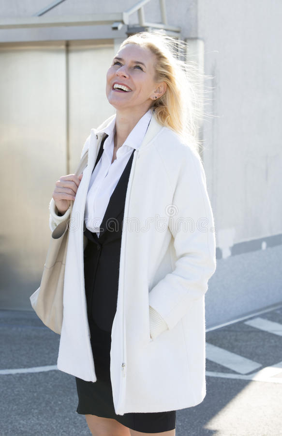 Женщина вне лифта усмехается стоковое фото rf