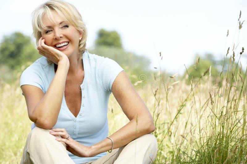 женщина возмужалого портрета сельской местности сидя стоковая фотография