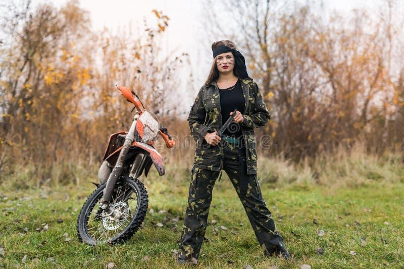 Женщина-воин в камуфляжной форме позирует на улице стоковые фотографии rf