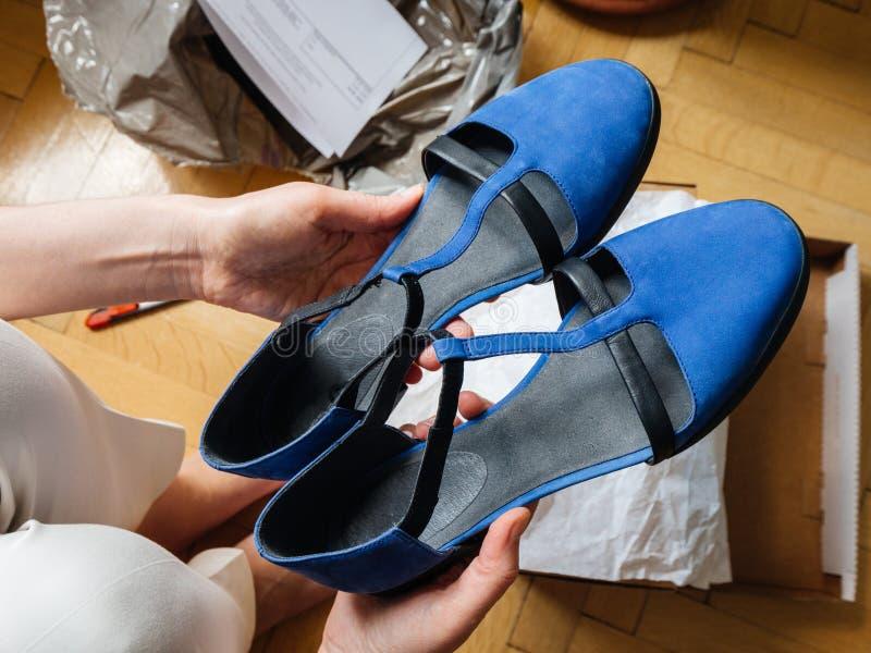 Женщина восхищая голубые ботинки после unboxing POV стоковое изображение rf