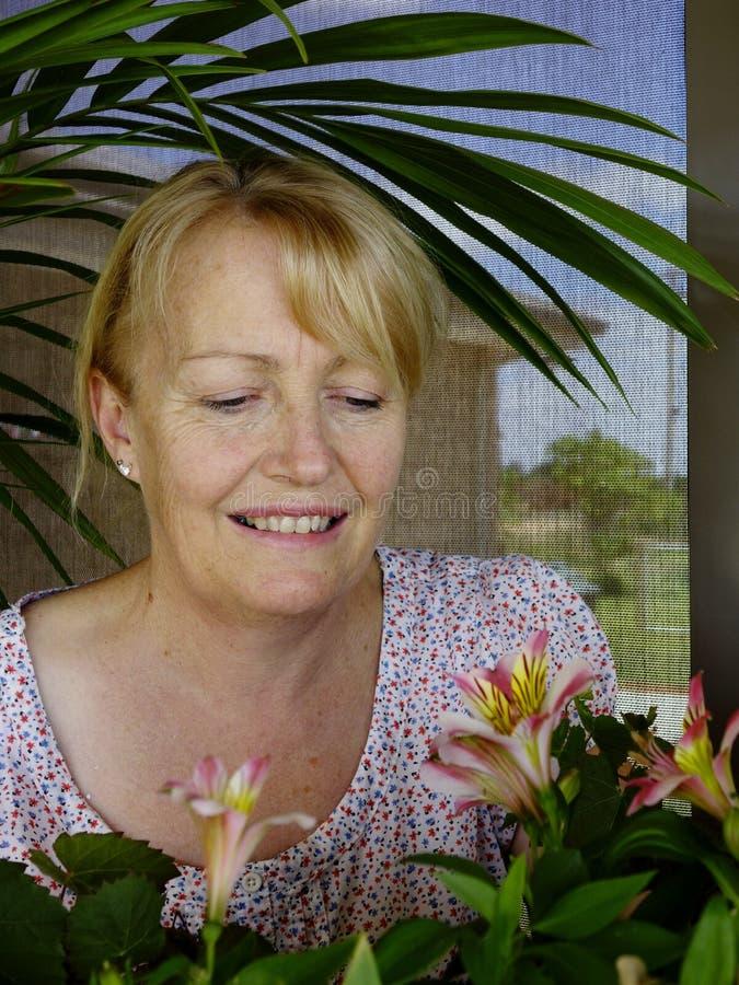 Женщина восхищая новые цветеня стоковое фото