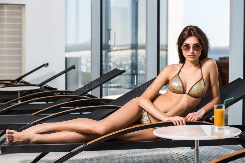 женщина воды спы здоровья ноги внимательности тела Женщина с совершенным телом в бикини лежа на deckchair бассейном стоковое фото