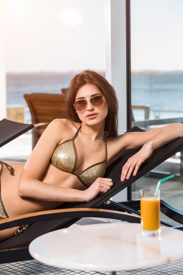 женщина воды спы здоровья ноги внимательности тела Женщина с совершенным телом в бикини лежа на deckchair бассейном стоковые изображения