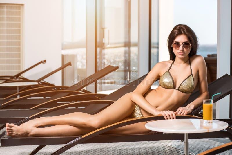 женщина воды спы здоровья ноги внимательности тела Женщина с совершенным телом в бикини лежа на deckchair бассейном стоковые фотографии rf