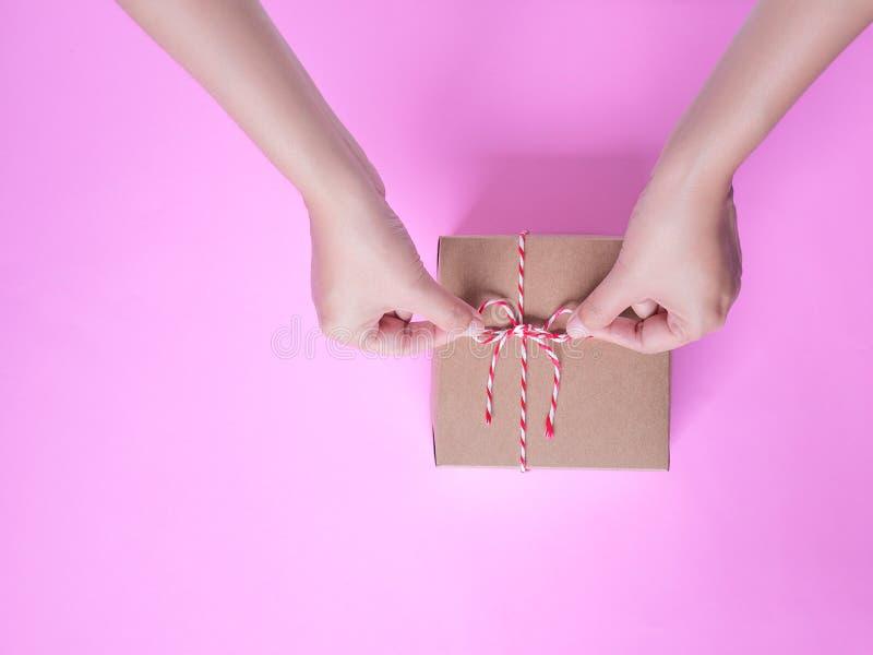 Женщина вручает бабочке простую обернутую подарочную коробку бумаги ремесла стоковая фотография