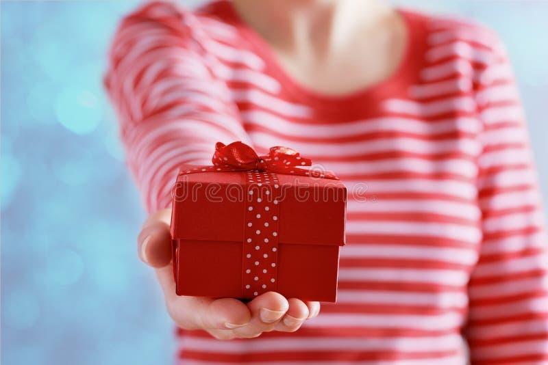 Женщина вручает держать подарок или присутствующую коробку с смычком красной ленты на день валентинок стоковая фотография