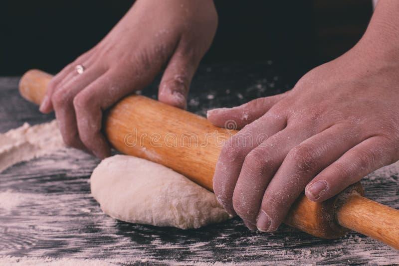 Женщина вручает разворачивание печенье с завальцовк-штырем стоковое фото