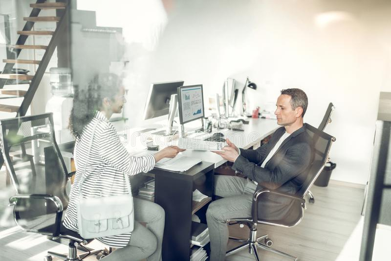 Женщина вручая ее CV к бизнесмену пока имеющ собеседование для приема на работу стоковые фото