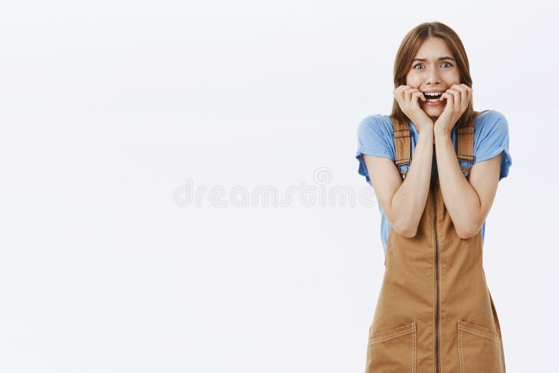 Женщина вспугнутая стиля причесок друга ужасного, дрожащ от зашкурить страха, паниковать и сдерживать ногтей устрашенный сверх стоковая фотография rf